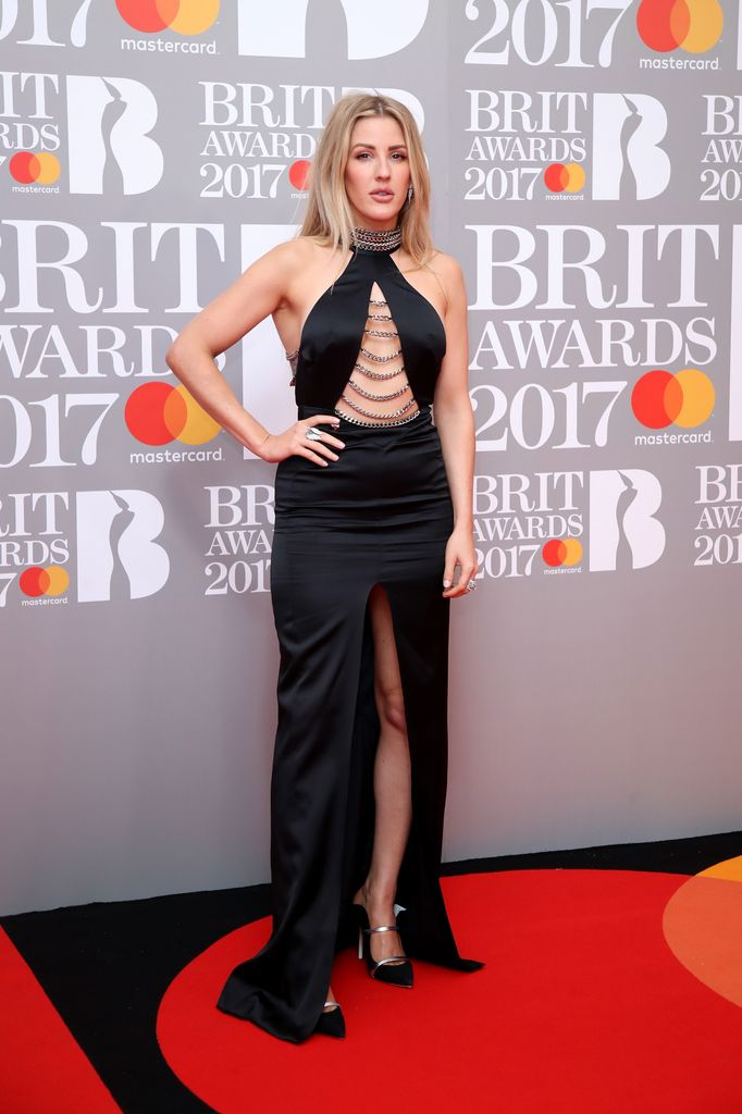 421a4853 One of the first stars on the red carpet, Ellie Goulding opted for a  halterneck satin black gown by Philipp Plein. The daring option came  complete with ...
