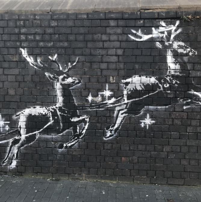 Reindeer pull homeless guy on workbench